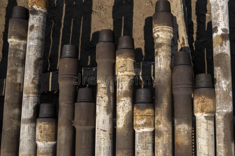 Oil Drill pipe. Rusty drill pipes were drilled in the well section. Downhole drilling rig. Laying the pipe on the deck. View of. The shell of drill pipes laid stock photo