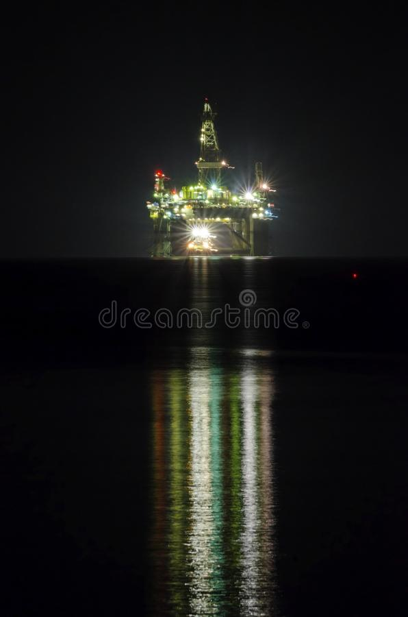 Oil drilling platform. A night view of the oil drilling platform lit up on the coast of Limassol, in Cyprus. The oil rig is floating in the Mediterranean sea and stock image