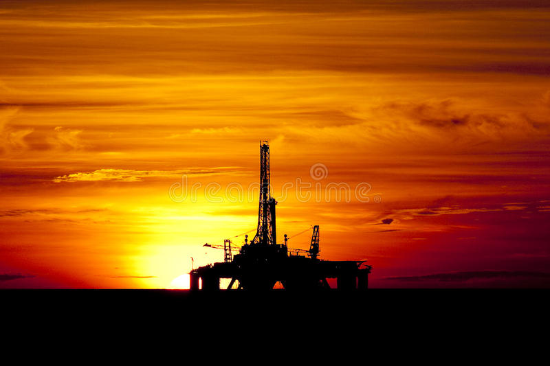 Oil Drilling rig in sunset time. Shadow of an oil production drilling rig, in offshore area, during sunset ttime in the coast off Brazil stock photos
