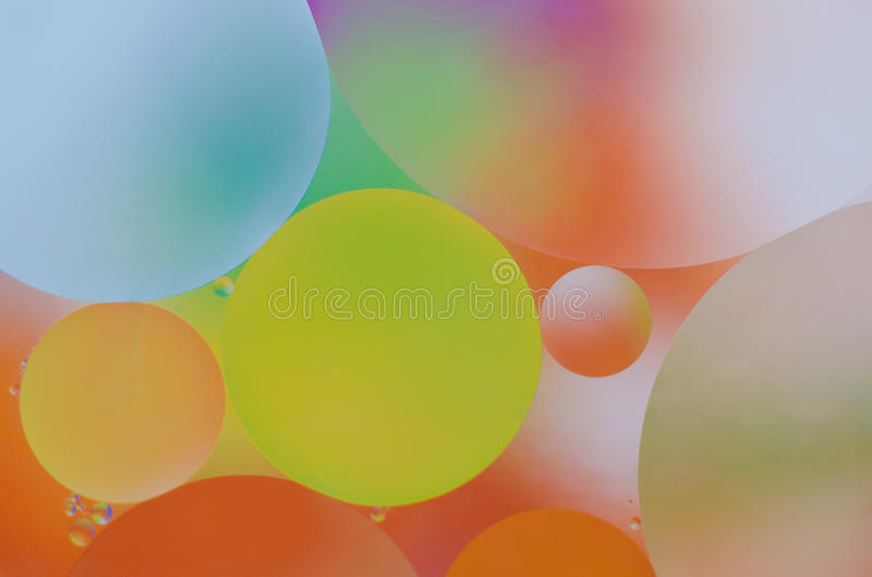Oil drops on water. Colored oil droplets on the water surface stock photography