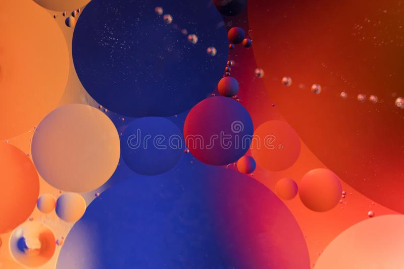 Oil drops in water on a coloured background stock photos