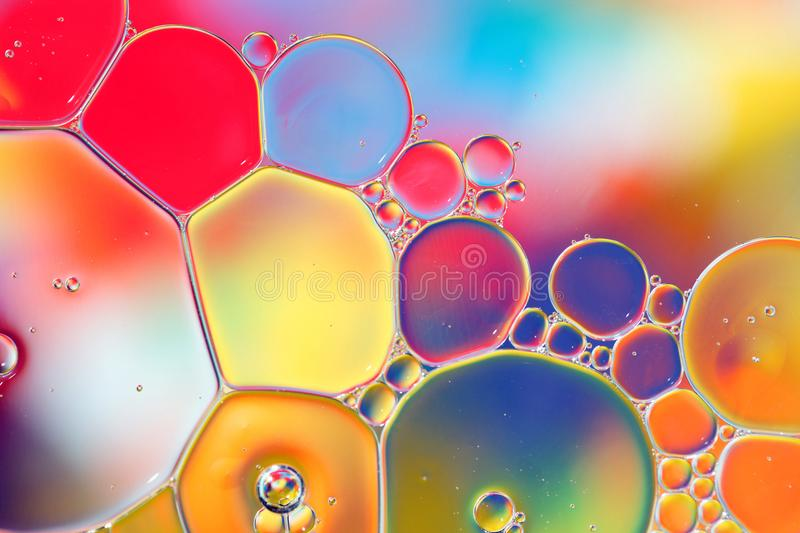Oil drops in water on a coloured background stock photo