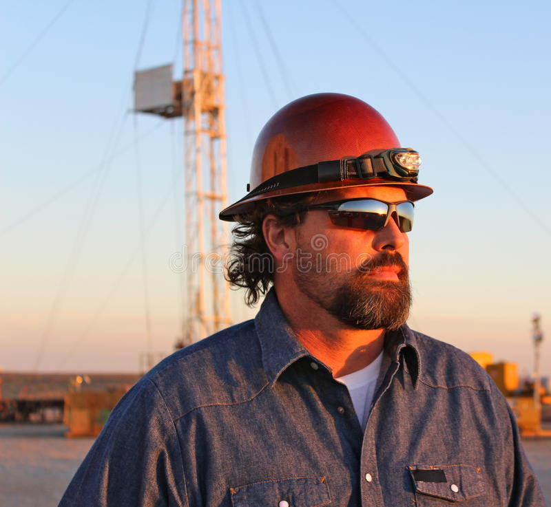 Oil field. Worker watching the sunset royalty free stock photo
