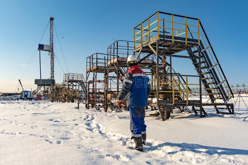 Oil field with oilman running along the wells. Oilman, is on the northern field along oil producing wells. In the background, a drilling rig. Winter. Sunny day royalty free stock photography