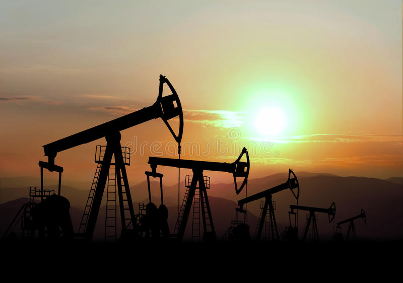 Oil field. And pump jack on sunset royalty free stock image