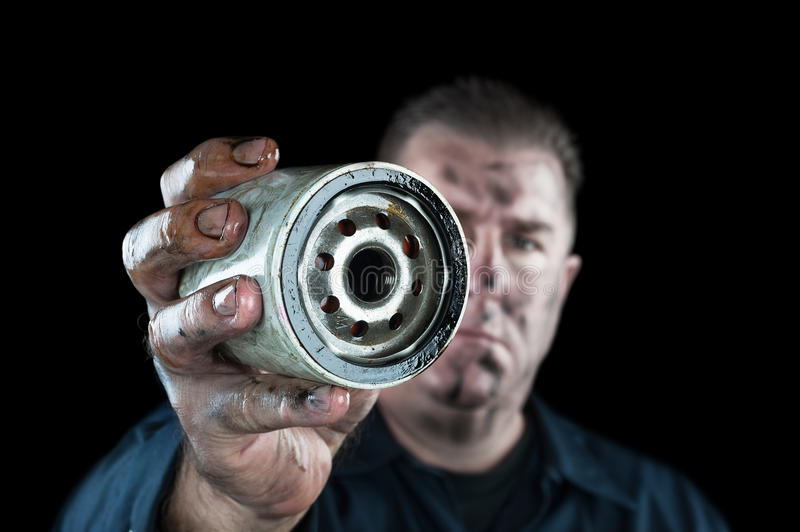 Oil Filter. An auto mechanic showing a dirty oil filter during general car maintenance stock photography