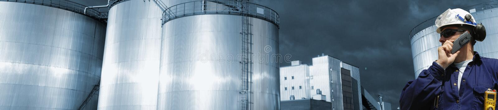 Oil and fuel storage with worker. Oil worker talking in phone, large fuel storage towers in the background, panoramic view royalty free stock image