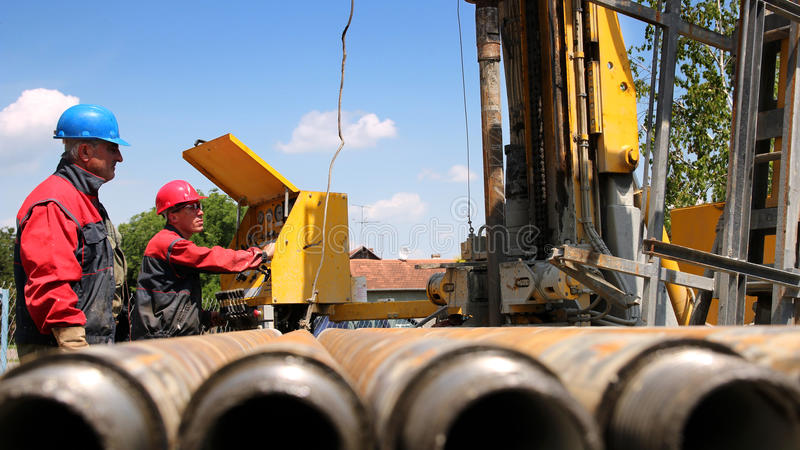 Oil and Gas Drilling Rig. Oil drilling rig workers lifting drill pipe stock photo
