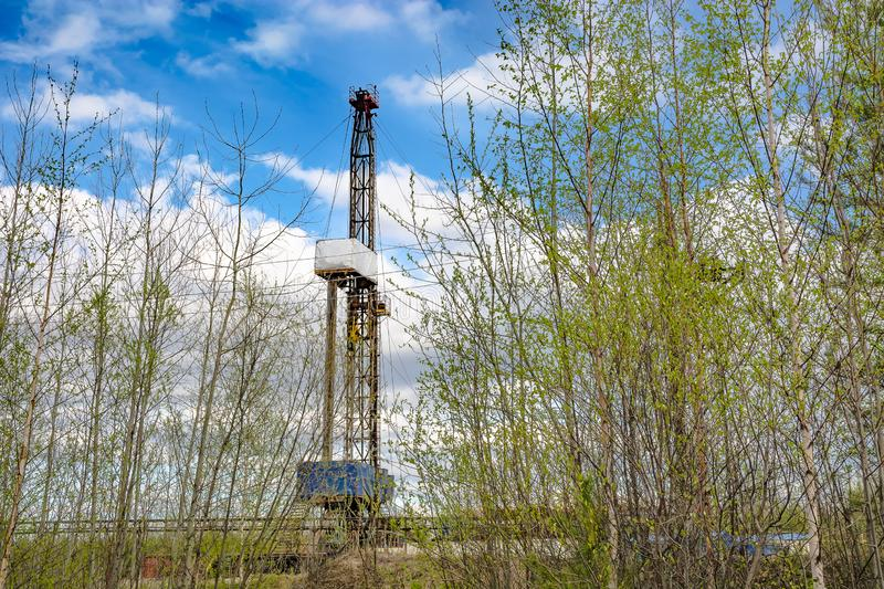 Oil and gas drilling rig in front of spring trees. Oil and gas drilling rig in the background in focus. In the foreground, young trees in the spring are out of royalty free stock images