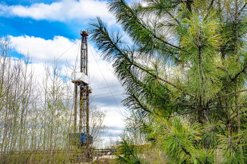 Oil and gas drilling rig in front of spring trees. Oil and gas drilling rig in the background in focus. In the foreground, young trees in the spring are out of stock photo