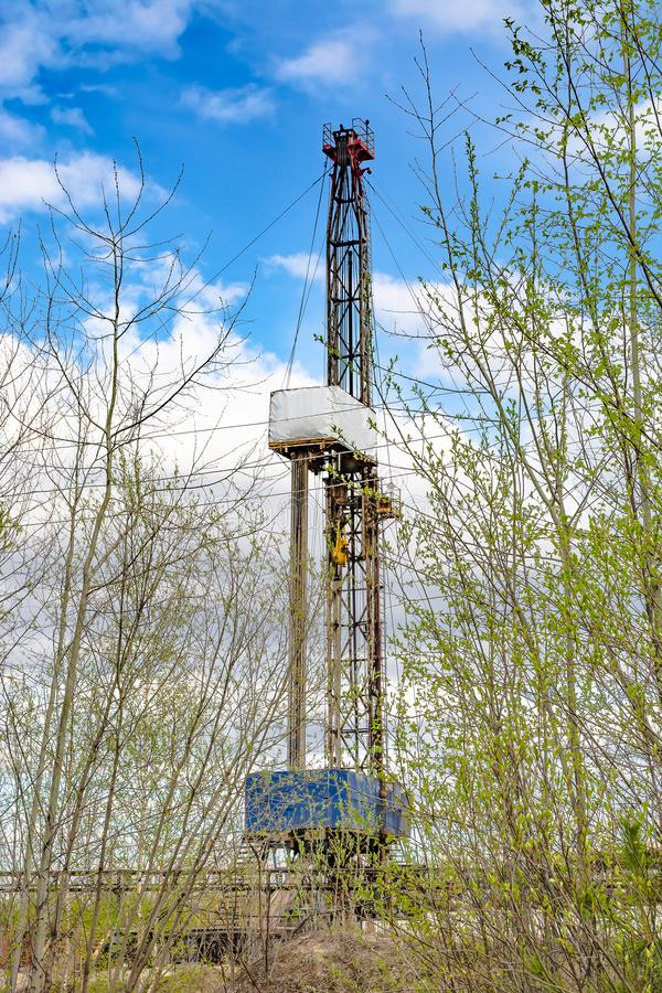 Oil and gas drilling rig in front of spring trees. Oil and gas drilling rig in the background in focus. In the foreground, young trees in the spring are out of stock image