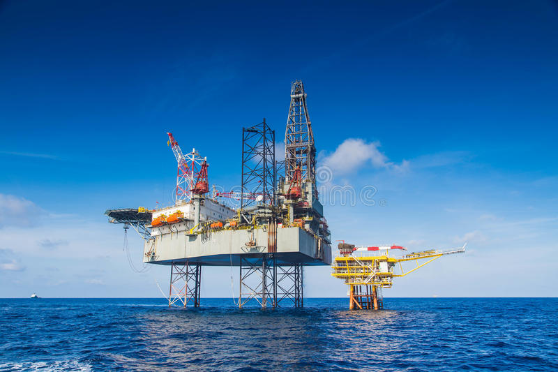 Oil and gas drilling rig work over remote wellhead platform to completion oil and gas produce well. By using drilling bit which made from carbide or diamond at royalty free stock photography