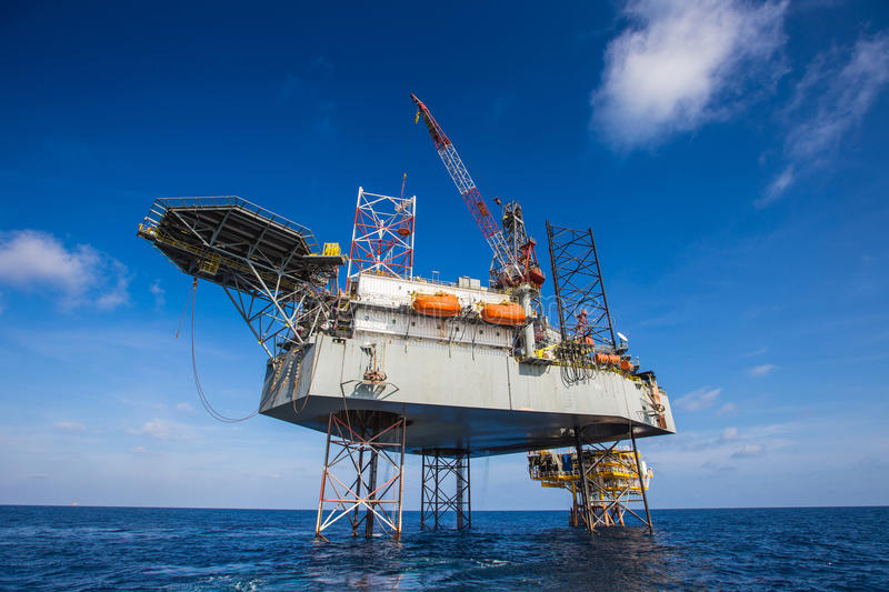 Oil and Gas drilling rig working on remote wellhead platform, prepare to transfer passenger by personal basket.  royalty free stock images