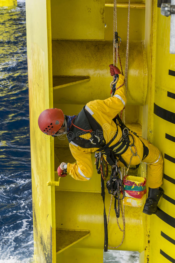 Oil and gas industrial occupational. Working overboard. A commercial abseiler complete with Personal Protective Equipment PPE hanging at oil and gas platform royalty free stock photo