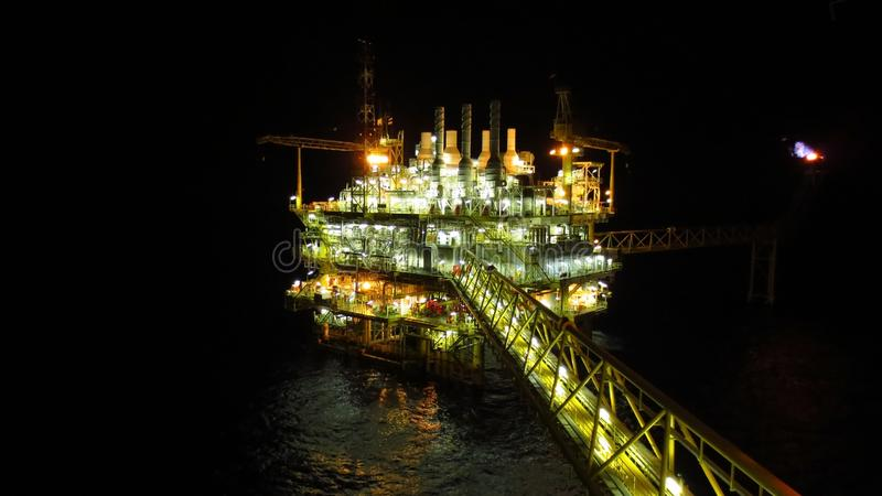 Oil and gas industry and hard work at night time. Offshore construction platform stock photography