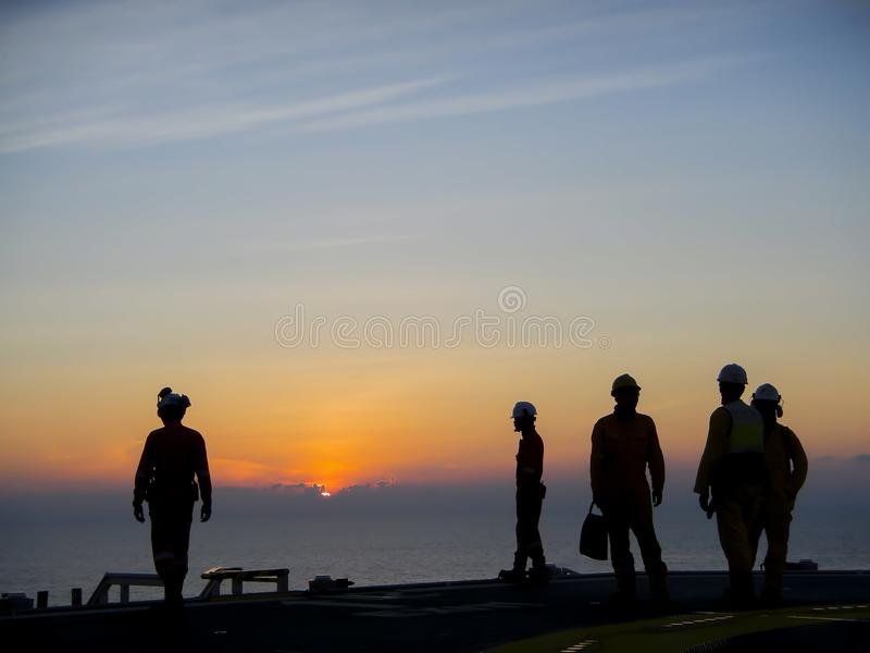 Oil and gas industry. Silhouette of offshore workers on helideck during sunset royalty free stock photos