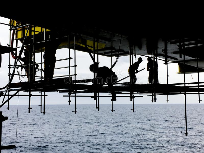 Oil and gas industry. Silhouette of offshore workers with fall p. Rotection device working overboard below oil and gas platform in the middle of the sea stock photography