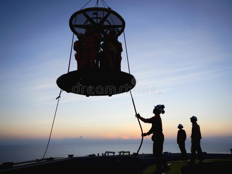 Offshore Transportation. Oil and gas industry. Silhouette of offshore workers standing on helideck area to use Personal Transfer Basket PTB for transferring from royalty free stock photography