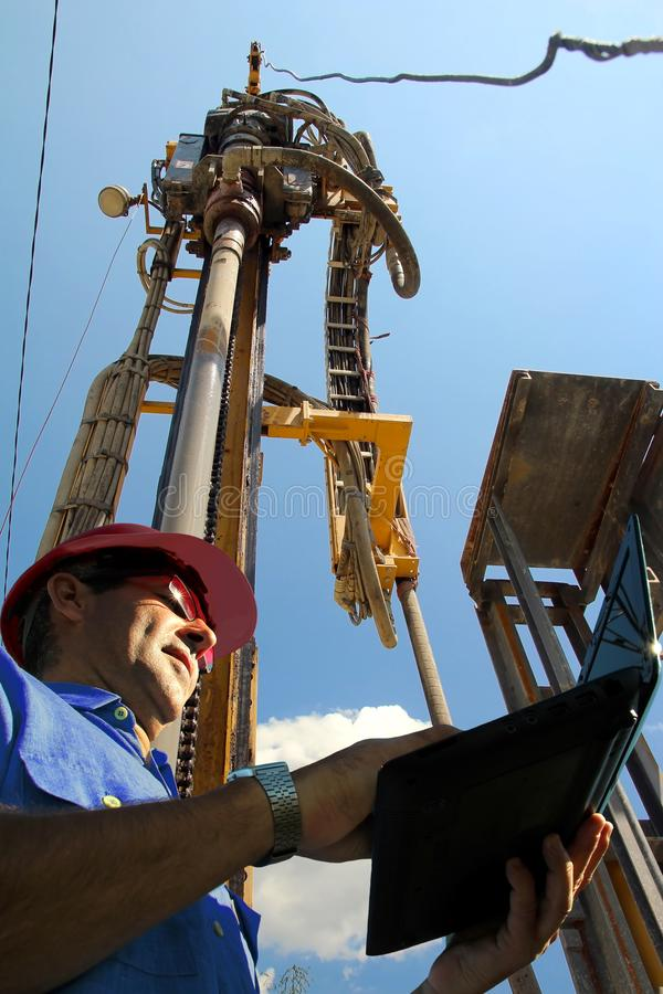 Oil And Gas Industry Specialist. Petroleum engineer with laptop computer in an oilfield. Oil and gas engineering royalty free stock photos