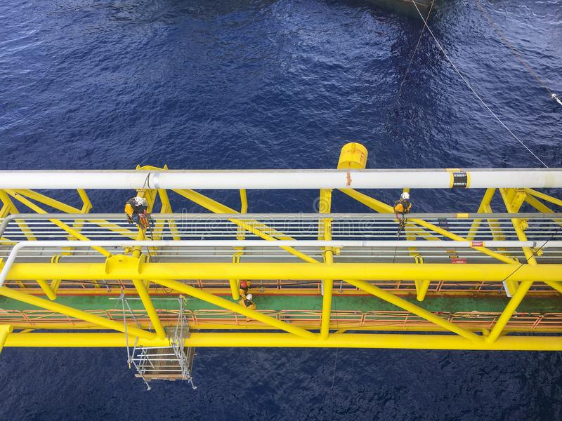 Oil and gas industry. View of oil and gas pipeline on the bridge structure in the middle of the sea while a group of abseiler with Personal Protective royalty free stock photos