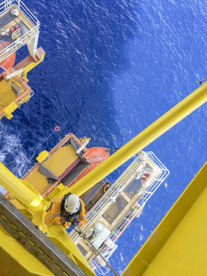 Oil and gas industry. Working at height. Working overboard. Oil and gas industry. A commercial abseiler with fall protection device hanging at the edge of opil royalty free stock image