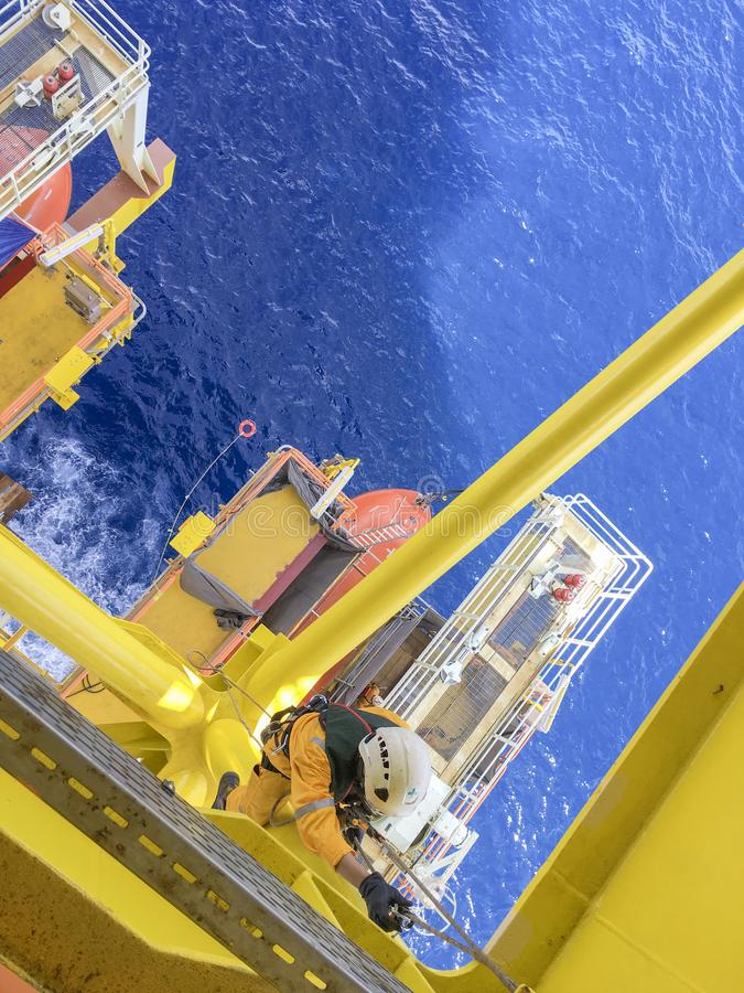 Oil and gas industry. Working at height. Working overboard. Oil and gas industry. A commercial abseiler with fall protection device hanging at the edge of oil stock photo