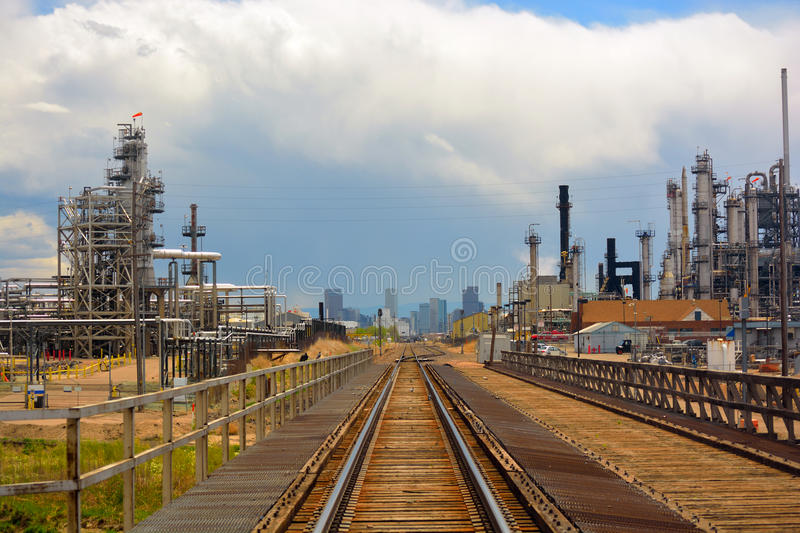 Oil and Gas Refinery Distillation Towers with Railroad Tracks and a Distant City stock photo