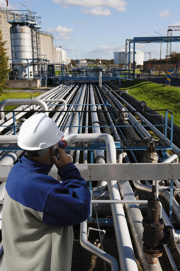 Oil and gas worker in front of refinery. Oil and gas worker standing in front of a giant oil-refinery, panoramic view stock photos