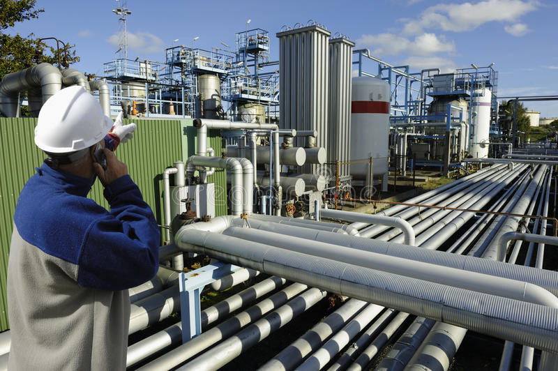 Oil and gas worker with pipelines. Oil and gas worker with large refinery pipelines constructions stock images