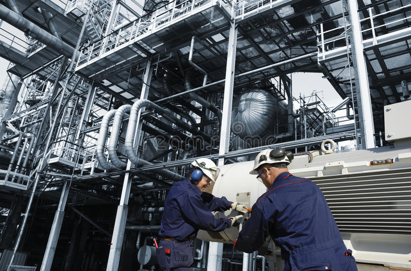 Oil and gas workers inside refinery. Two oil and gas workers inside large refinery royalty free stock images