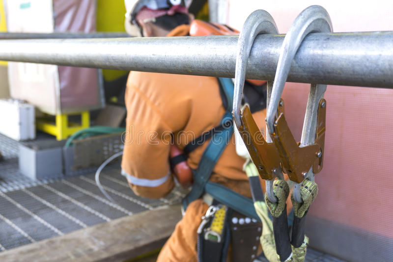 Oil and gas. Working at height equipment. Fall arrestor device for worker with double hooks for safety body harness on selective focus. Worker as a background royalty free stock photos