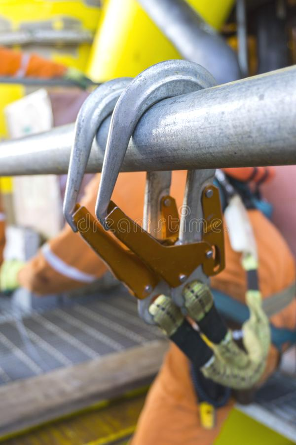Oil and gas. Working at height equipment. Fall arrestor device for worker with double lanyard and hooks at galvanized tube for safety body harness on selective royalty free stock image