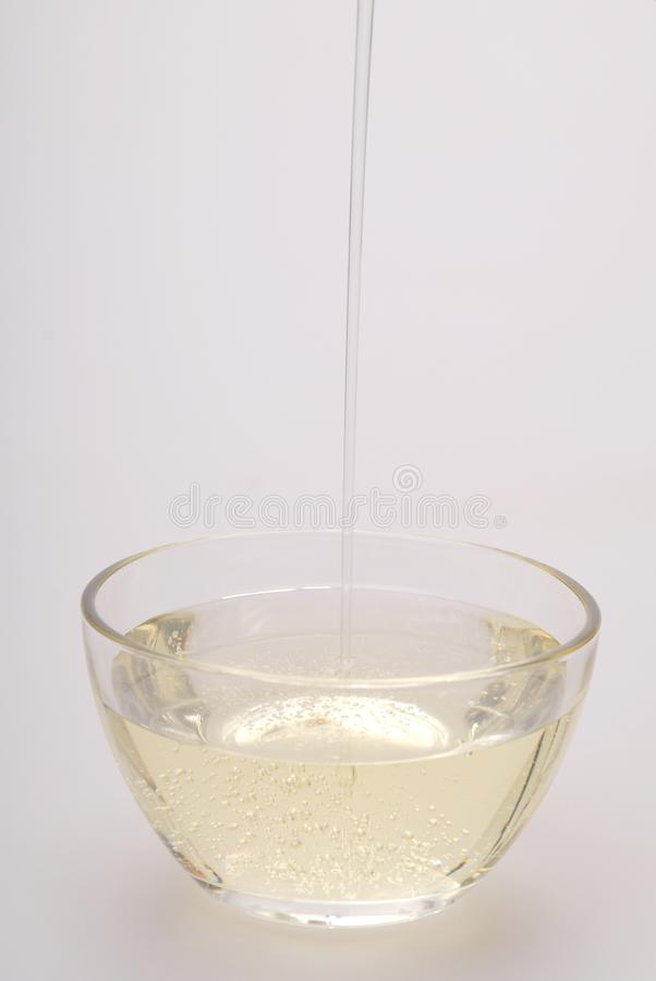 Oil into a glass bowl. Pour sunflower . Isolated on a grey background stock image