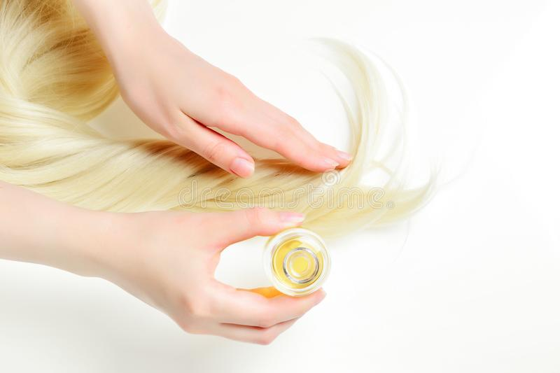 Oil hair treatment for woman with blond hair on white background. Spa, beauty salon. royalty free stock photography