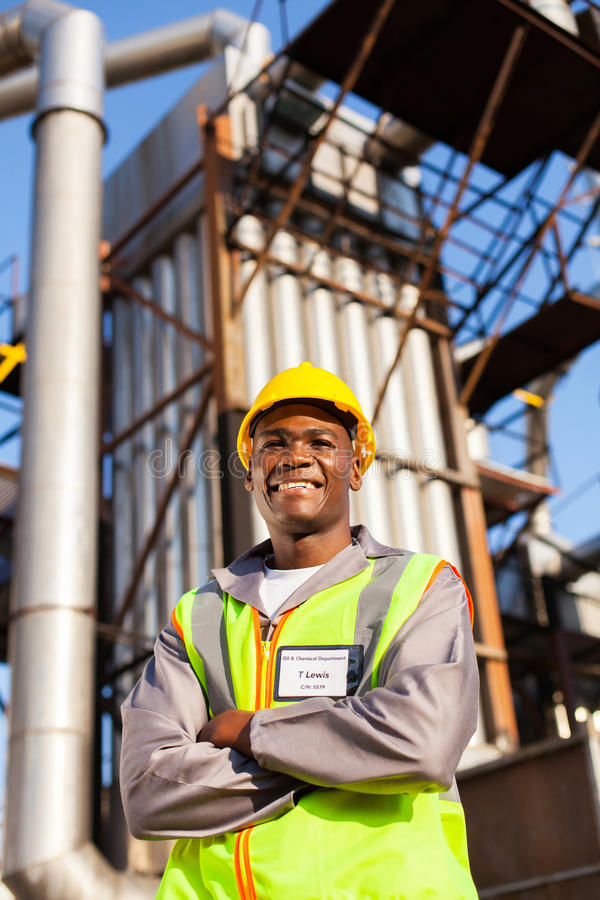 Oil industrial worker. Cheerful afro american oil industrial worker with arms crossed in refinery plant stock photography