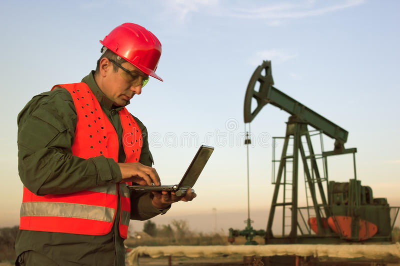 Oil Industry. Pump jack with one oil worker who using a laptop royalty free stock photography