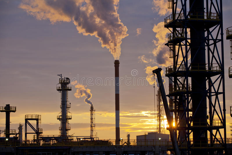 Oil Industry Refinery factory at Sunset. Petroleum, petrochemical plant smoke comes out of big chimneys after processing and combustion of oil royalty free stock images