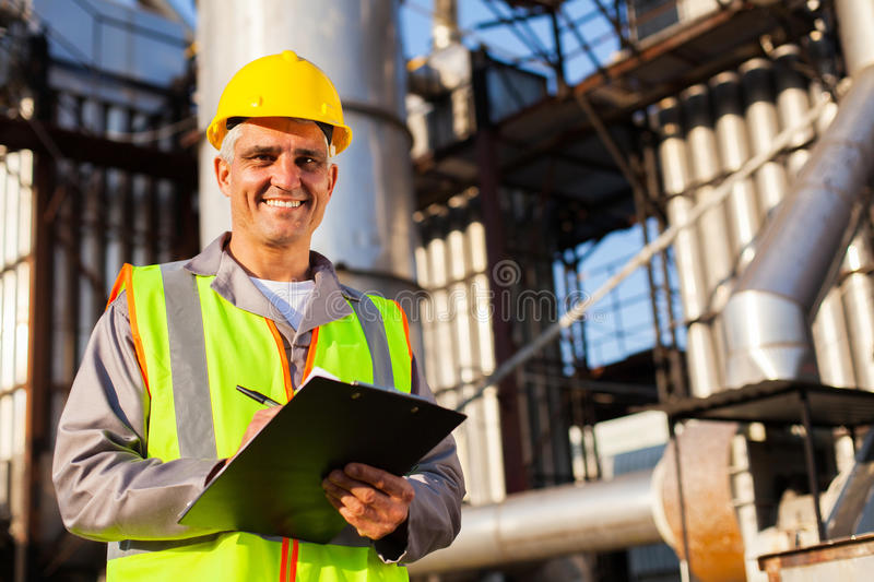 Oil industry worker. Happy middle aged oil industry worker in refinery plant stock images