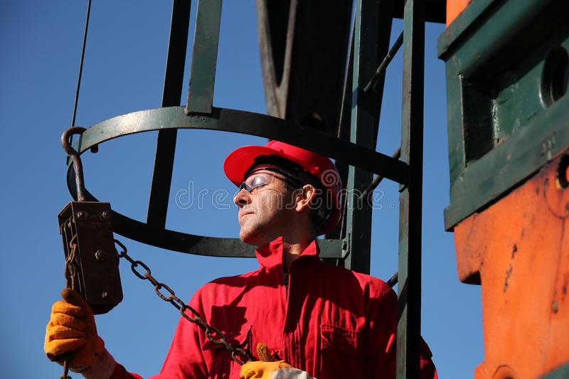 Oil Industry Worker Using Chain Winch. Oil industry worker in action with chain winch at pump jack oil well royalty free stock image