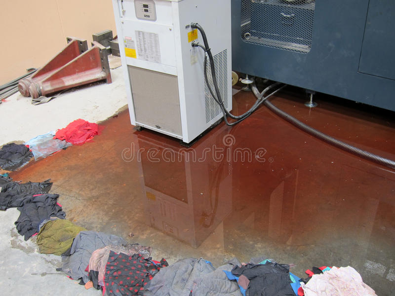 Oil leak. Lubrication oil leak from under the CNC machine royalty free stock photo