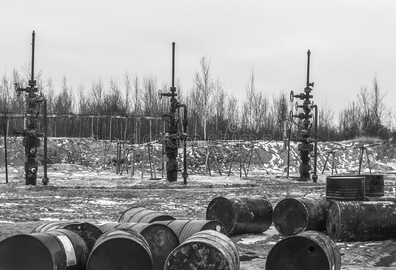 The oil is over. There is nothing to fill barrels. Empty barrels from the oil before the stopped oil wells. Ecological problem in the field stock photo