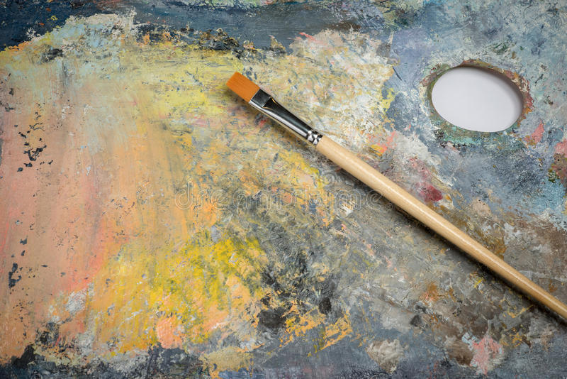 Oil paint on a palette and brushes. Oil paint of different colors on a palette and brushes stock photography