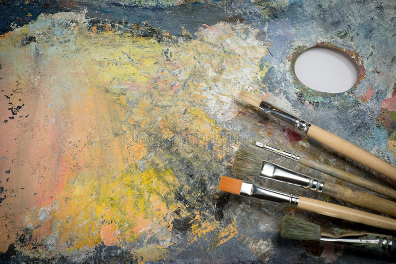 Oil paint on a palette and brushes. Oil paint of different colors on a palette and brushes royalty free stock photo