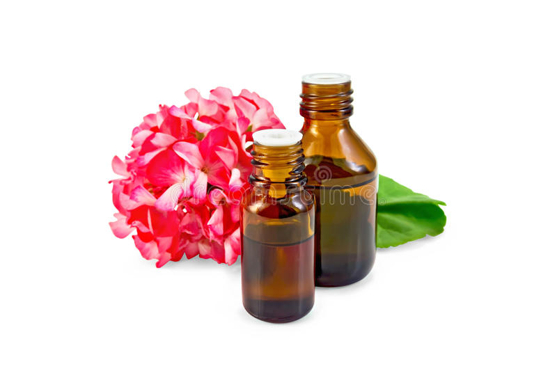 Oil with pink geraniums in two dark bottles royalty free stock photos