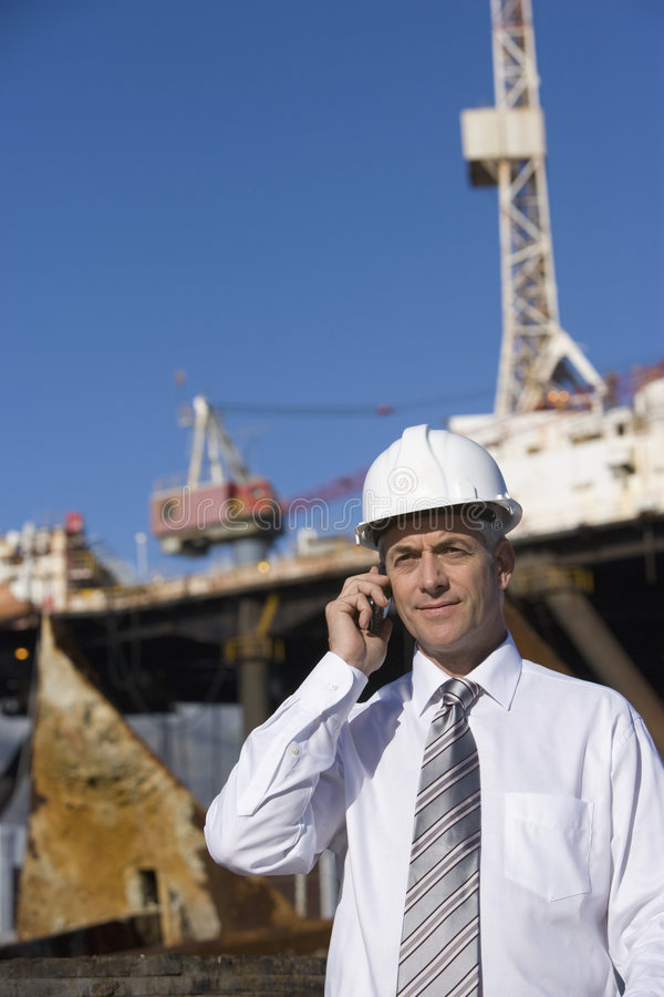 An oil platform inspector. On the phone, with the platform in the background stock photo