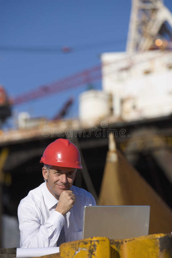 An oil platform inspector with his laptop. With the platform in the background stock images
