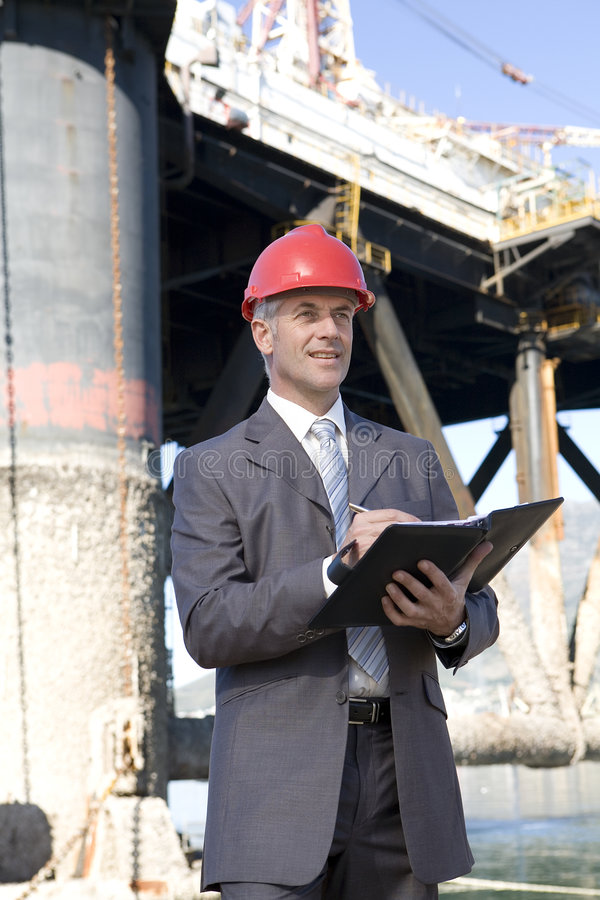 Oil platform inspectors. Oil platform inspector with oil rig behind royalty free stock photography