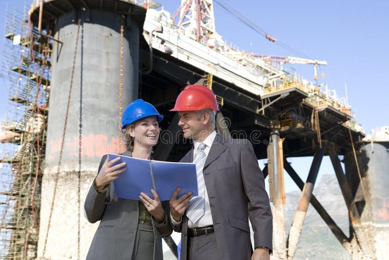 Oil platform inspectors. Two oil platform inspectors with oil platform hehind royalty free stock photo