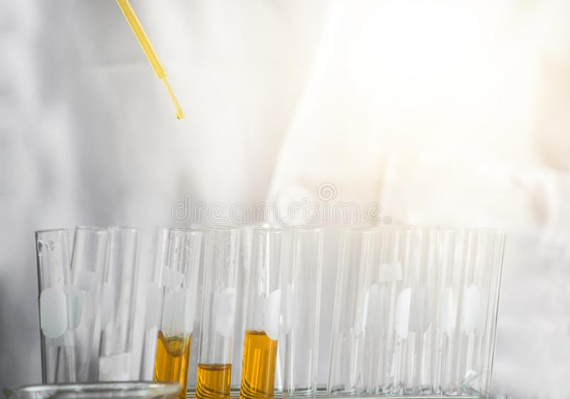 Young Asian scientist with test tube making research in clinical laboratory.Science, chemistry, technology, biology and people con. Oil pouring, Formulating the stock image