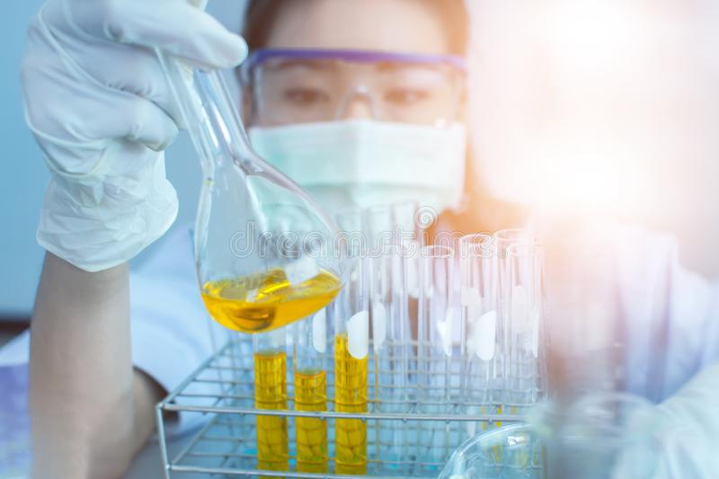Young Asian scientist with test tube making research in clinical laboratory.Science, chemistry, technology, biology and people con. Oil pouring, Formulating the stock photography